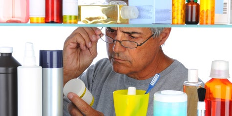 Man searching through medicine cabinet and examining label of medicine