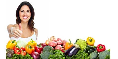 Woman holding her thumb up in front a mixed, colorful area of vegetables like bell peppers, broccoli and more