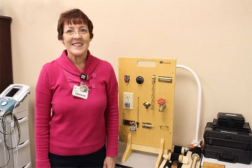 Marta Brinkley, an occupational therapist at Andrews Institute standing in front of equipment.