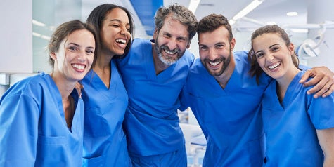 Five people working in the medical professional world gathering and smiling