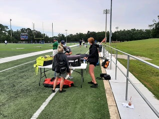 Athletic Trainers working on the sidelines of a UWF football practice.