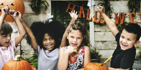 Kids enjoying carving pumpkin for halloween.