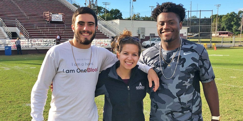Athletic Trainer poses with student athletes at local high school.
