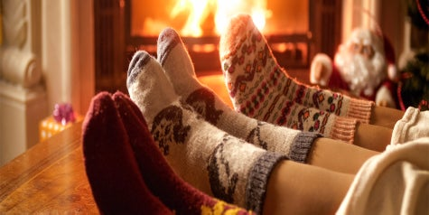 Three sets of feet wearing socks by the fireplace