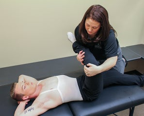 Athletic trainer stretching the leg of a ballet dancer on a therapy table.