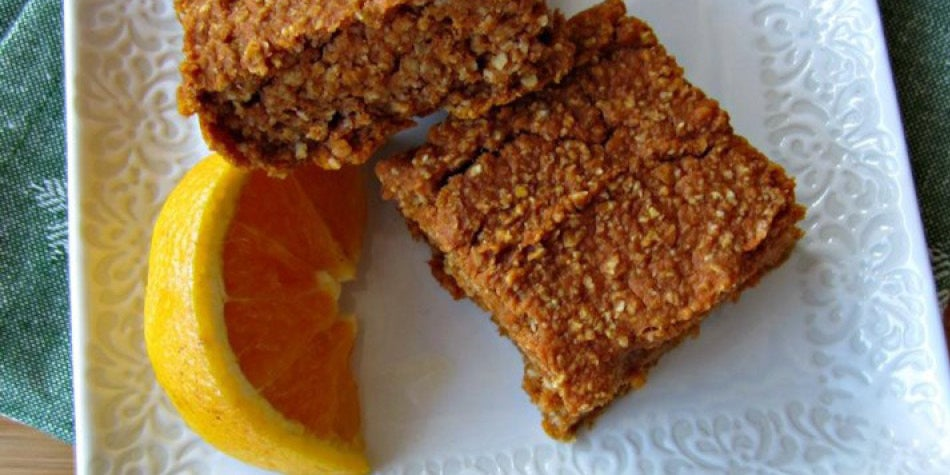 Pumpkin oat bar with slick of lemon on plate.