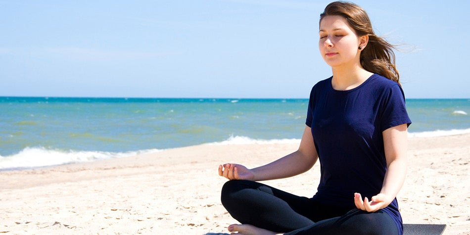 Woman sitting on beach with legs crossed meditating and practicing yoga