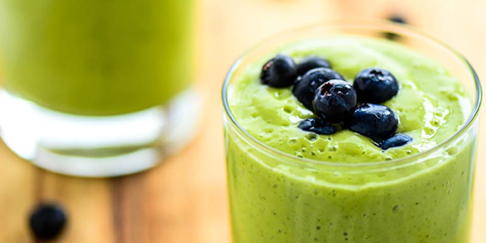 Green drink filled with fruits and veggies, topped with blueberries