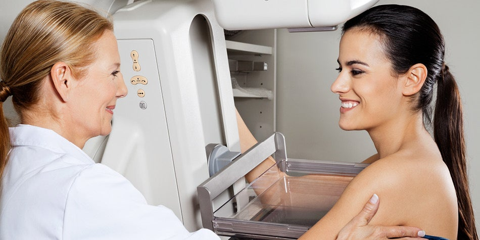 Woman is having a mammogram. Two women are pictured - one using machine and one on the machine for her screening.