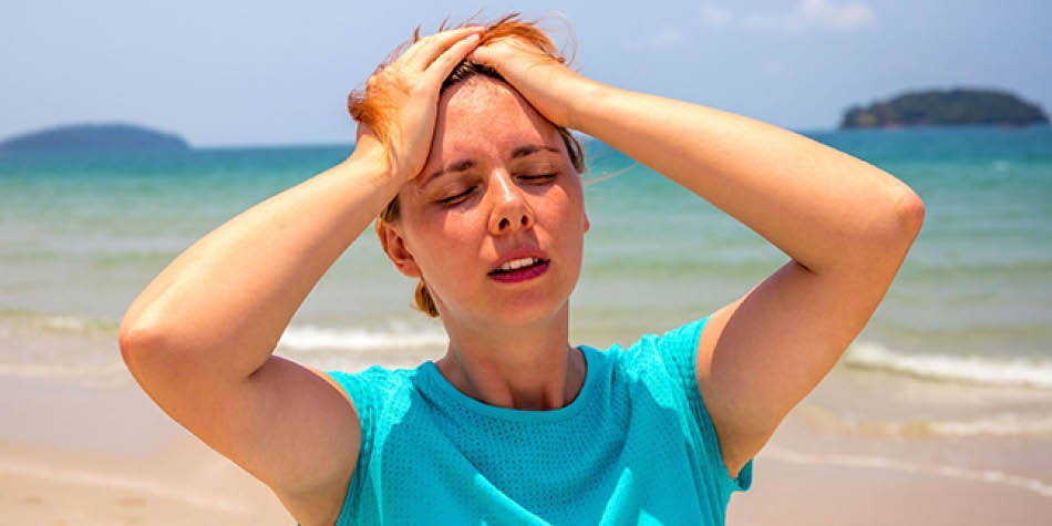 Woman looking overheated outside at the beach