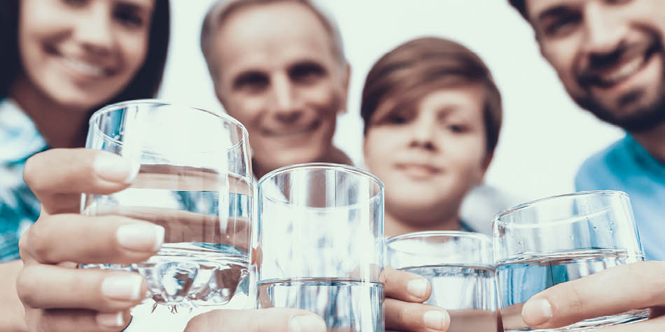 Family holding up glasses of water ready to drink