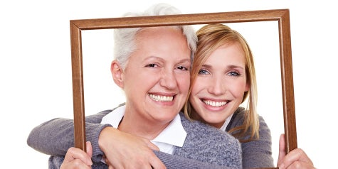 Mother and daughter looking through empty frame