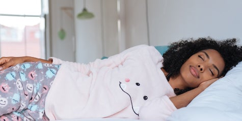 Women in pink pajamas sleeping peacefully in bed.