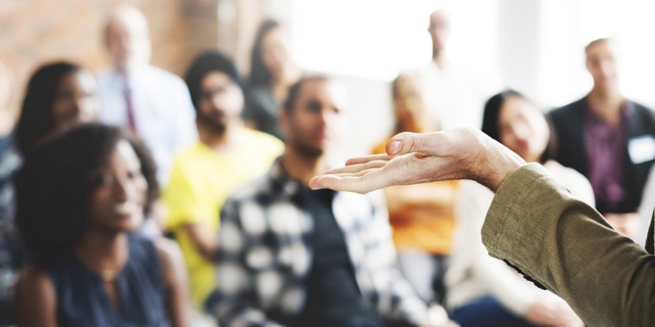 A group discussion and forum setting with people listening to one person speak