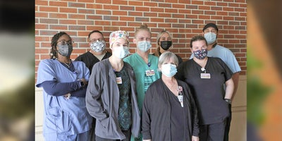 Lab department team members standing outside in a group wearing masks
