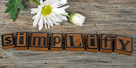The word simplify is written in blocks with a daisy flower next to it.