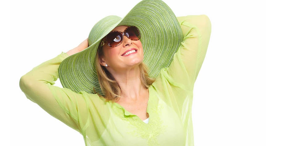 Woman wearing green had and sunglasses smiling.