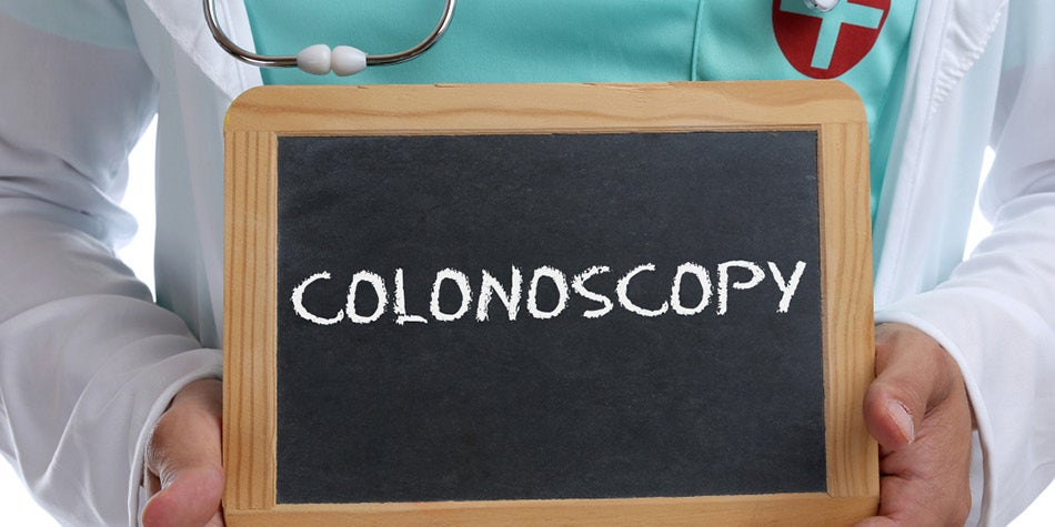 Medical professional holding up a colonoscopy sign