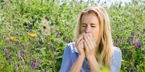 Woman sneezing due to outdoor allergies