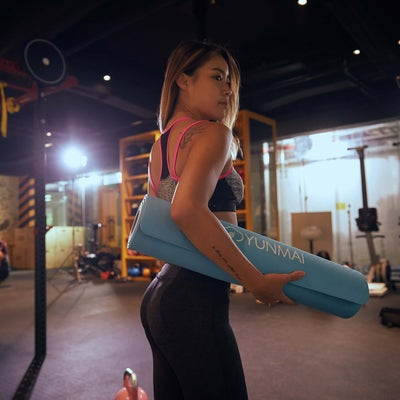 girl holding yoga mat in a gym