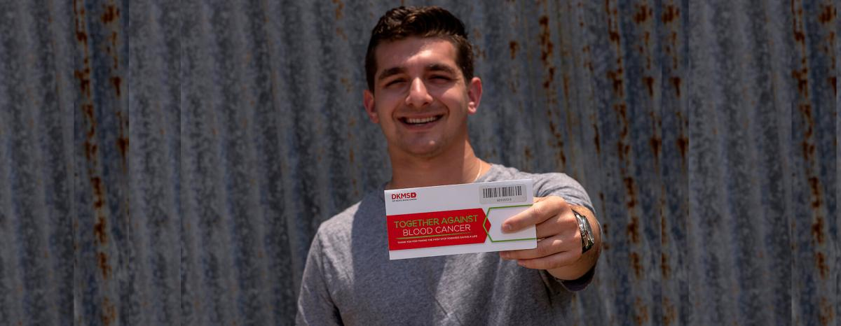 Cody Donor holding DKMS envelope kit