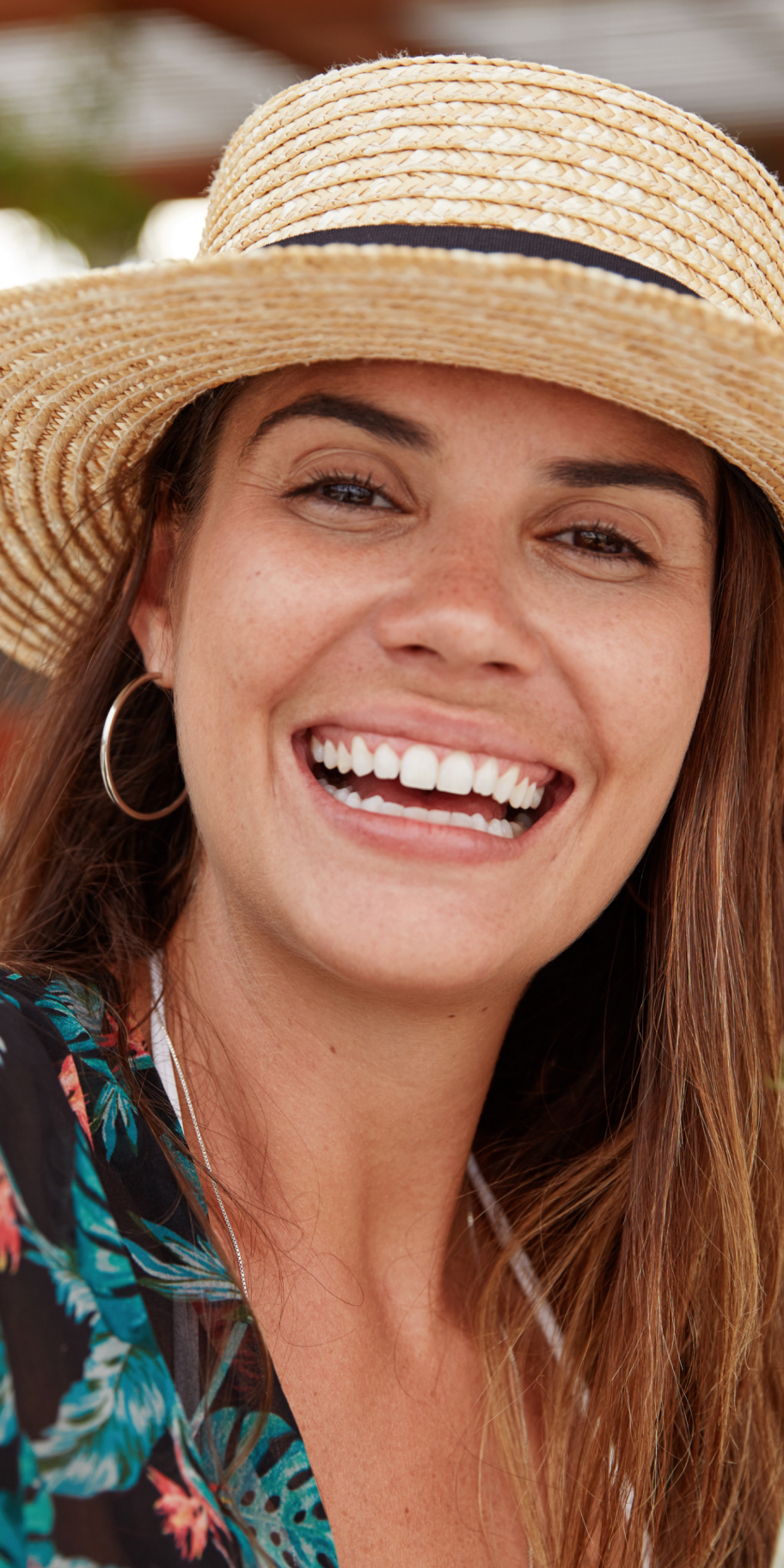 Woman wearing a hat smiling about to receive a gift card