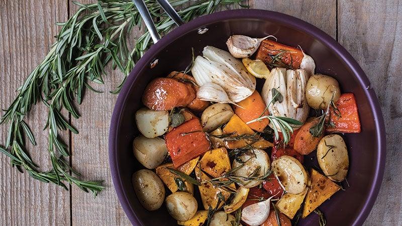 A purple non-stick frying pan with vegetables in on a wooden table with a bunch of rosemary.