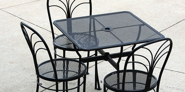 A black outdoor table and chair set protected from the daily wear and tear of water and chemical corrosion by PPG coatings.
