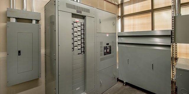 Utility room containing gray switchgear and electrical enclosures