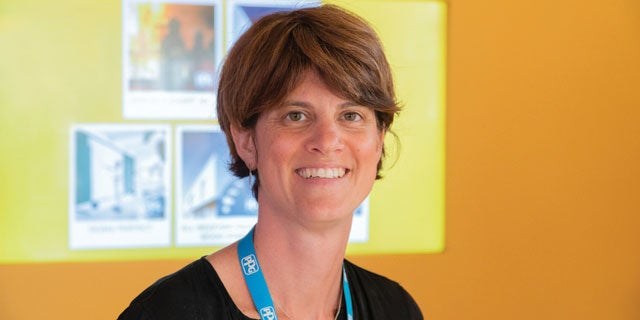 Emeline Firmin, PPG's Ultra Violet-Electron Beam and wood coatings lab manager, smiling in front of orange background.