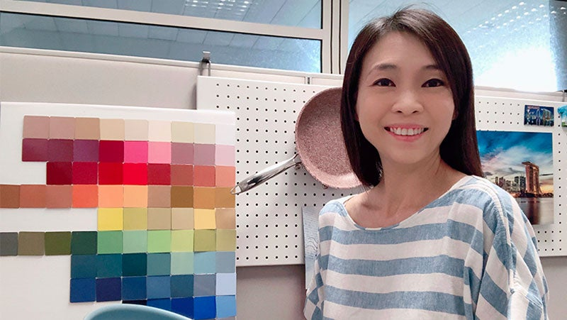 Karen Tyng Cowell, PPG's APAC marketing manager, smiling with color swatches from PPG's kitchenware coatings and a pink frying pan.