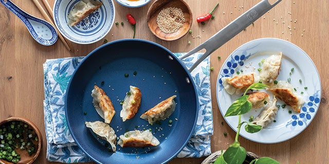 Gyoza in blue non-stick frying pan, protected by PPG's non-stick coatings, surrounded by ingredients in bowls.