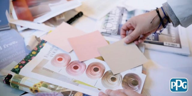 PPG color stylist holding color swatches against a home styling magazine.