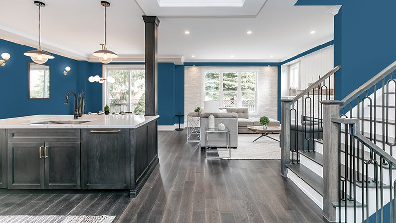 Blue and white living room and kitchen with beige grey wood finishes.