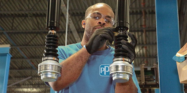 PPG technician wearing a blue PPG t-shirt monitoring and cleaning coating machinery.