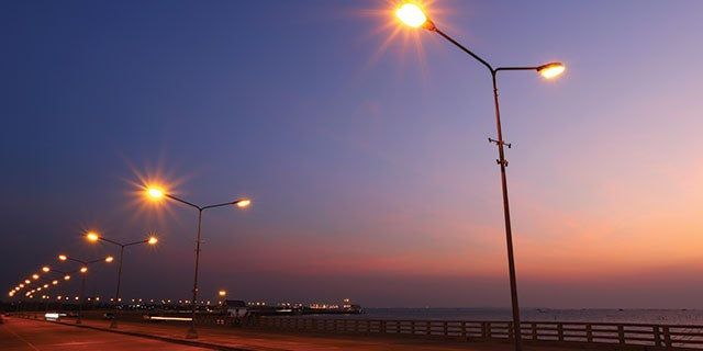 Streetlights on a road next to the sea at sunset. PPG delivers coating systems for outdoors with a range of effects and textures.