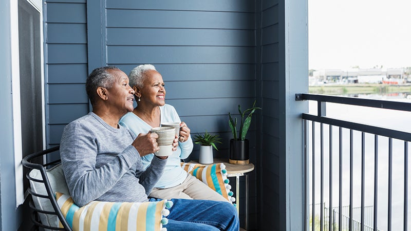 A couple sat on a balcony looking at the view and drinking from a mug each.