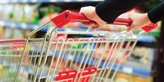 Close-up of person pushing a shopping cart with a red handle and seat in a grocery store.