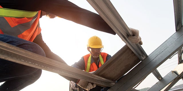 Two construction workers creating a metal framework protected by PPG's durable coating systems.