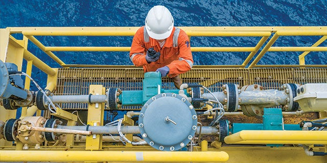 Engineer monitoring machinery on an offshore site that faces extreme conditions.