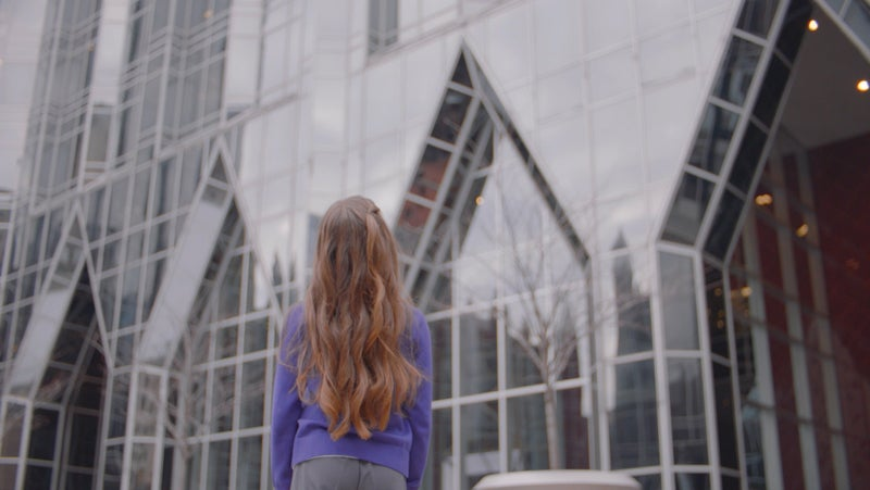 Young girl wearing purple sweat looking up at PPG's headquarters in Pittsburgh, Pennsylvania.