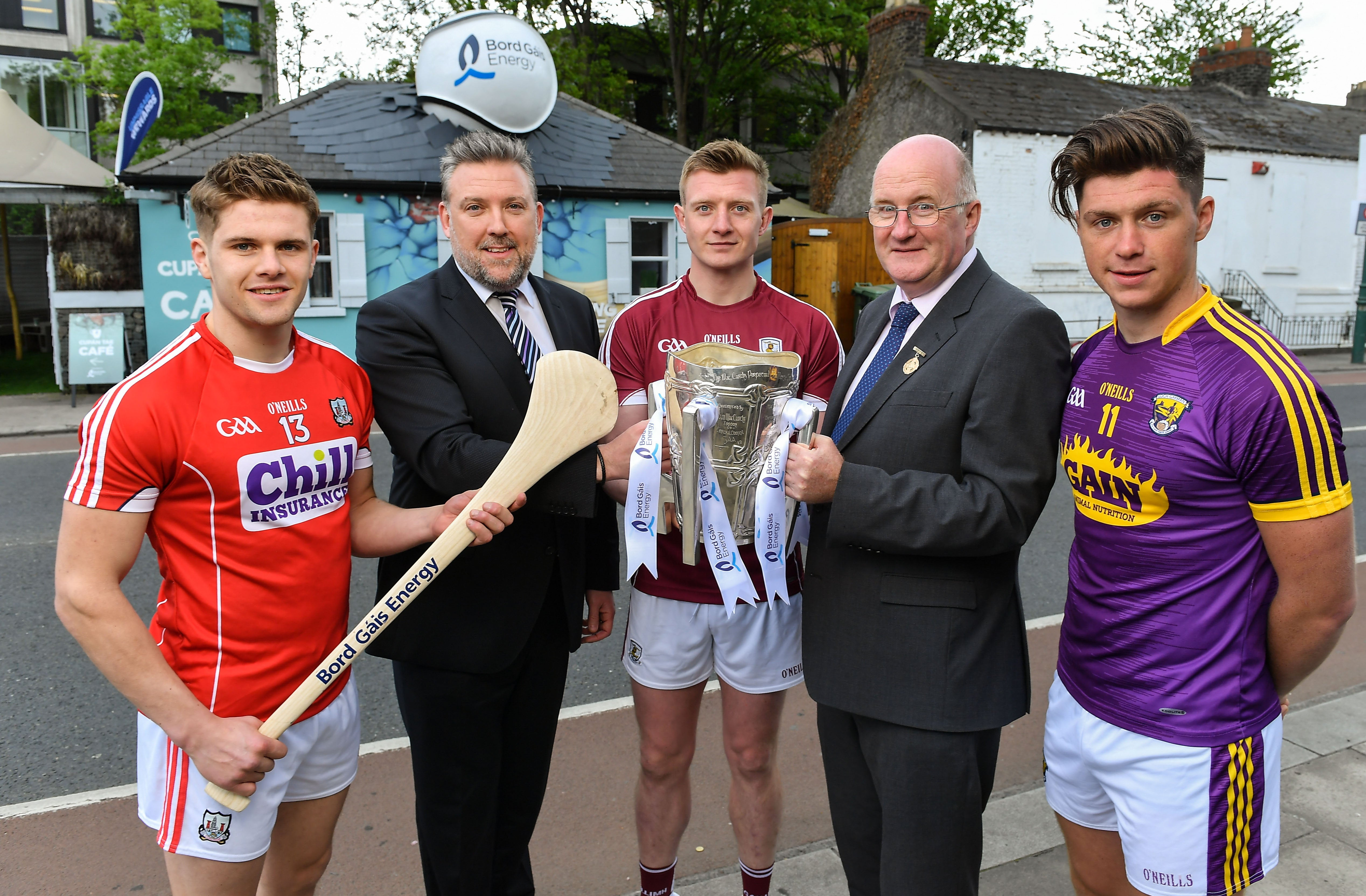 5 men standing outside a cafe: 3 county hurlers, one holding a hurl, one holding a trophy; 2 men in suits.