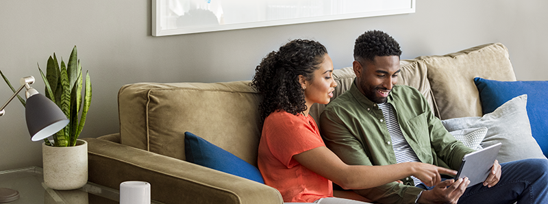Couple sitting on a couch looking at a laptop