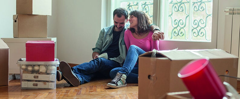 Couple sitting on the floor of a room surrounded by boxes