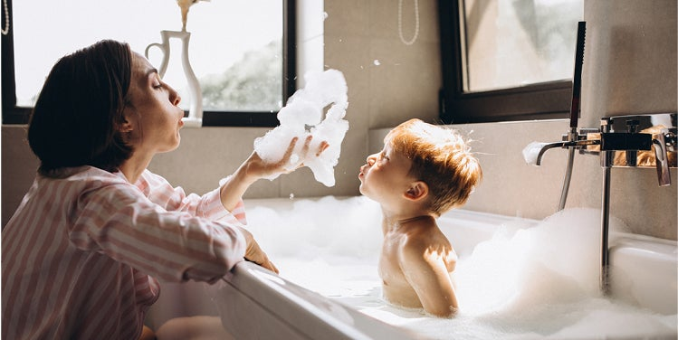 Woman with child in bath blowing bubbles