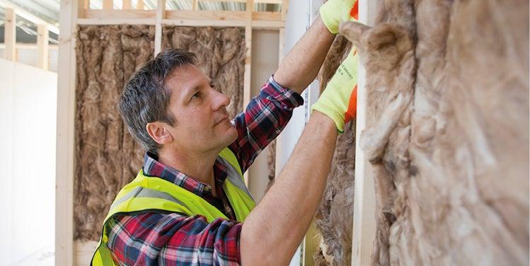 Male worker installing insulation