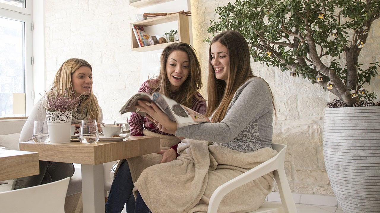 Vriendinnen die samen reclame folders lezen van CMN