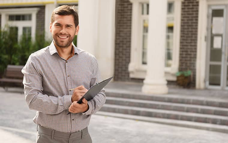 man in plaid shirt holding a clipboard