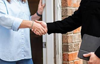 tech and homeowner handshake