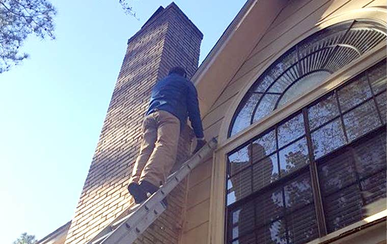 technician inspecting exterior of a home in spring texas